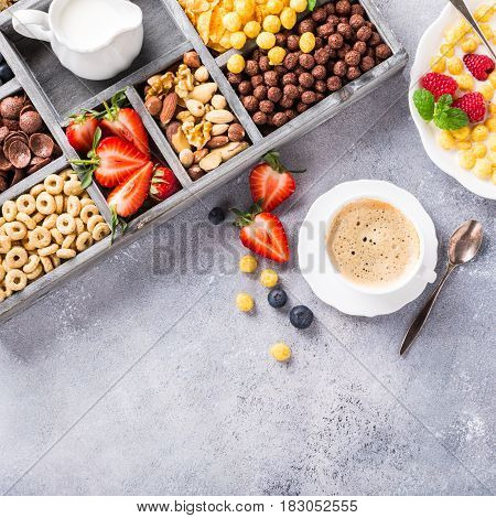 Healthy breakfast with coffee, variety of cold quick cereals and berries in old gray wooden box, selective focus. Copy space. Top view.