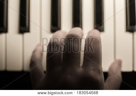 Closeup toned atmospheric photography of a hand playing the piano. Concept: Music creating, composing, lyrics