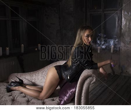 sexy young woman smoking electronic cigarette and lying on the sofa
