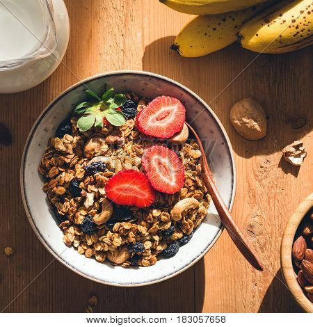 Delicious crunchy granola with nuts and raisins in bowl topped with fresh strawberries. Healthy breakfast food, morning sunlight, square crop.