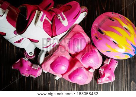 Pink skating rollers, protection and helmet on the wooden boards. Top view
