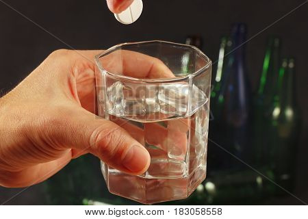 Hand with a soluble pill from hangover over a glass of water on a dark background.