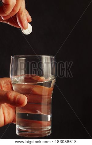 Hand with an effervescent tablet over the glass of water on a black background.