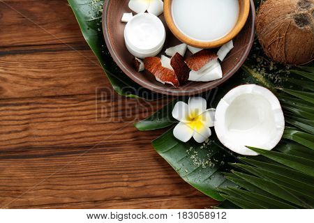 Composition with coconut milk and exotic flower on wooden background