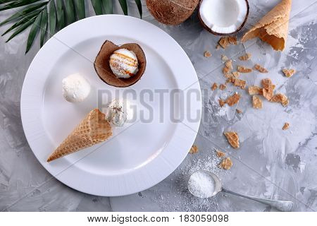 Plate with composition of ice cream balls in waffle cone and coconut shell on table