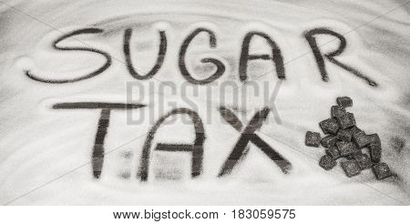 Sugar tax sign with sugar cubes in front