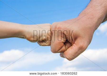 The fist of the child touches the male fist against the sky.