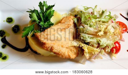 Photo of a delicious chicken schnitzel with salad in a cafe