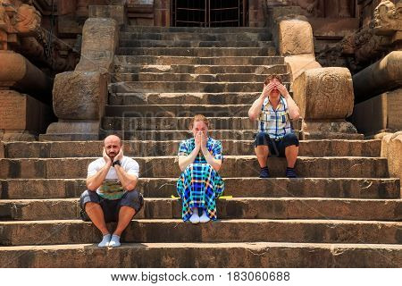 Group of tourists on the staircase of the temple depicts three mythical monkeys.