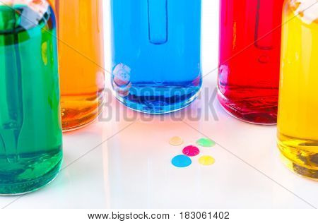 Colored drops and transparent glass bottles filled colored liquid with dropper. white background.