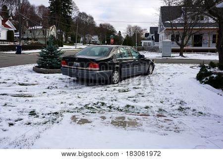 HARBOR SPRINGS, MICHIGAN / UNITED STATES - NOVEMBER 22, 2016: A black 1996 Mercedes Benz S420 luxury sedan is parked in the front yard of a home in Harbor Springs, after a November snowstorm.