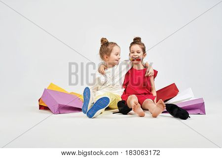 Two handsome little girls are starring at each other. Kids are sitting on the floor. There are lots of shoppers bags around them. Shopping, purchases, buy concept