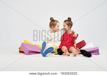 Pretty girls are laughing at each other. They are sitting on the floor with a mess of shopper bags. Next to them are oversized shoes. Shopping, purchases, buy, sale concept