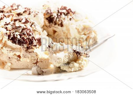 Meringue dessert on a white background. A dessert on a white plate a meringue piece on a teaspoon. Close up selective focus