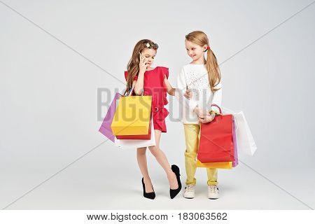 Two pretty girls are standing at the studio. One of them has over-size shoes and calling someone. Two best friends are holding shoppers bags. Shopping, purchases, buy concept