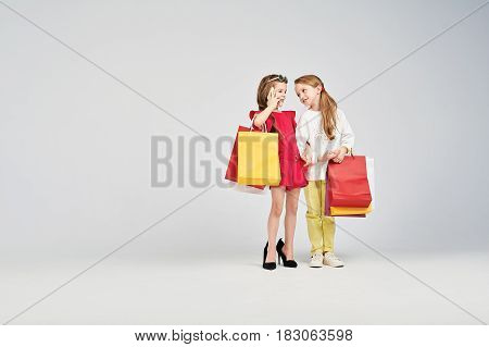 Two smiling girls are standing with shoppers bags. One of the is calling someone. One kid is wearing oversized shoes. Shopping, purchases, buy concept