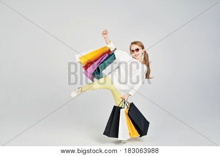Blonde girl in sunglasses in standing in a pose. She is laughing at the camera. Young lady has a lot of shoppers bags. Shopping, purchases, buy, sale concept