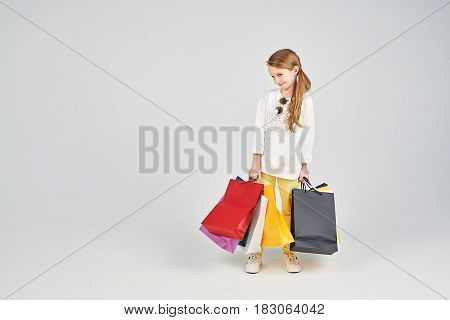 Little girl is a bit shy. Young lady s standing with a lot of shoppers bags. Shopping, purchases, buy, sale concept