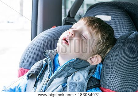 Little boy sleeping in child car seat. The chair is very comfortable. A boy wearing a blue jacket and gray. Boy wearing safety belts. He closed his eyes and opened his mouth.