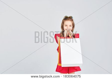 Pretty smiling girl is holding colorful shoppers bags. Shopping, purchases, buy, sale concept