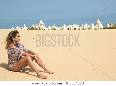 Pretty young brunette sitting in the desert with a palace on the background