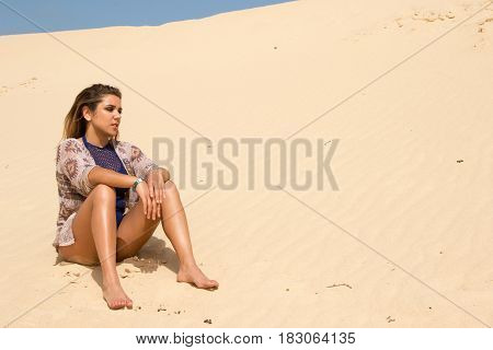 A lone woman sitting thinking in the sand