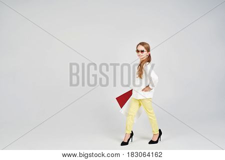 Young lady is posing to the camera in oversized shoes. Little girl in sunglasses in holding shoppers bags. Girl is Imitating adult women.
