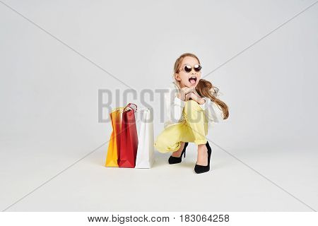 Young girl in sunglasses is sitting on the floor with an opened mouth. There are shoppers bags near her. Shopping, purchases, buy, sale concept