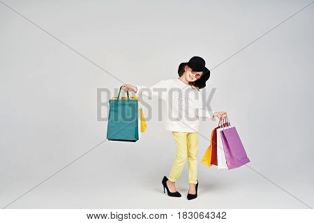 Little girl is wearing oversized hat and shoes. Young lady is holding variety of colorful shopper bags. Shopping, purchases, buy, sale concept