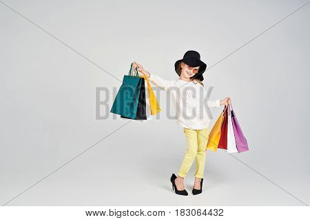 Little girl is wearing oversized hat and shoes. She is showing to the camera that she has lots of colorful bags in her arms. Girl is Imitating adult woman. Shopping, purchases, buy, sale concept