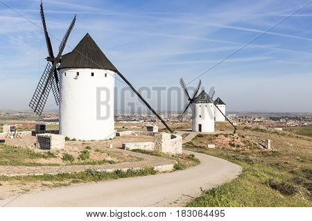 white windmills and a view of Alcazar de San Juan town, province of Ciudad Real, Castilla-La Mancha, Spain