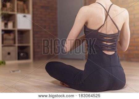 Back view of woman sitting in yoga lotus pose relaxing and meditating in living room.