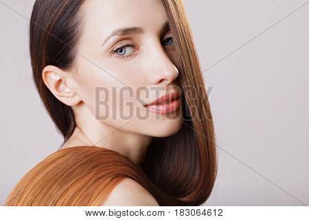 Beautiful model girl with shiny brown ombre straight long hair . Care and hair products . Grey background