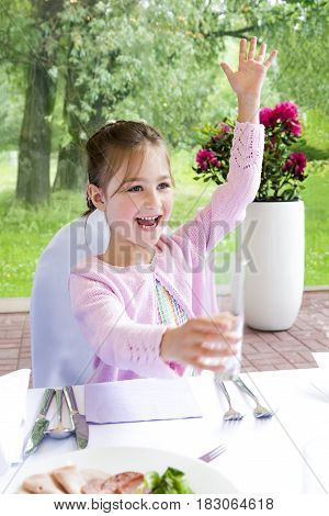 Cute smiling little girl calling waiter in a a restaurant.