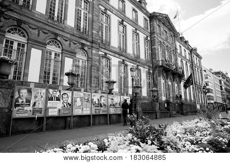 STRASBOURG FRANCE - APR 23 2017: Black ethnicity man and caucasian woman admiring official campaign posters for all eleven candidates for the 2017 French presidential elections posted outside a polling station at City Hall pooling station