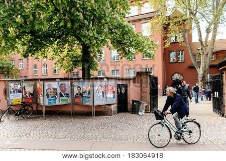 STRASBOURG FRANCE - APR 23 2017: Cyclist in front of French presidential campaign posters during first election day in France