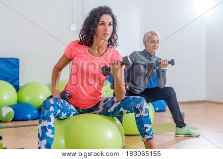 Close-up view of fit young brunette female exercising with dumbbells sitting on swiss ball during group fitness class.