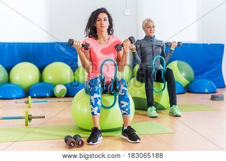 Slim sporty women training sitting on exercise balls holding dumbbells and squeezing Pilates Ring between their legs during group fitness studio class indoors.