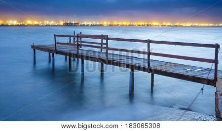 Long exposure of an old jetty on a river with city lights in the background