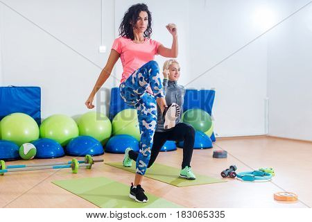 Two athletic female friends working out in a gym doing reverse lunge knee-up exercise.