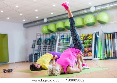 Fit athletic female doing single leg bridge exercise on mats at group classes in gym against bright sport equipment.