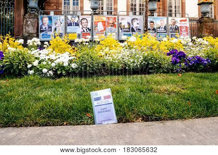 STRASBOURG FRANCE - APR 23 2017: Carte Electorale - voter's card French voter registration card is seen in front of official campaign posters for all eleven candidates for the 2017 French presidential elections outside pooling station