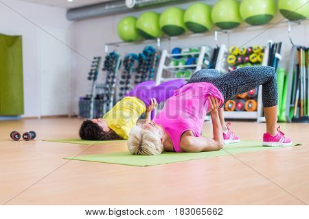 Group of women lying on floor on mats doing bridging exercise to firm buttocks indoors in fitness club.
