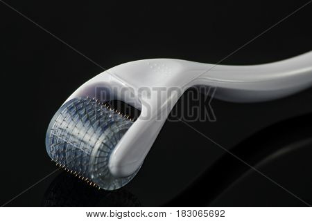 Dermaroller for medical micro needling therapy on black background. Tool also known as: Derma roller, mesoroller, meso-roller, mesopen.
