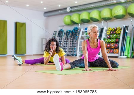 Fit women doing stretching exercises for legs and warming-up on floor before work-out indoors in gym.