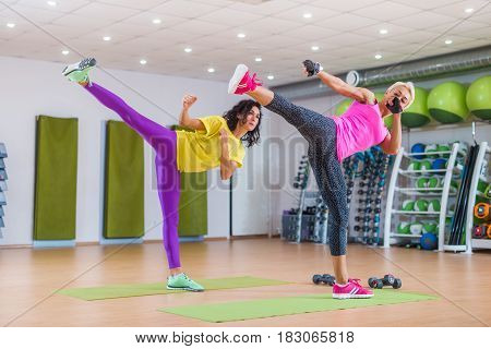 Fitness female instructors practicing sidekick exercise wearing bright sportswear training indoors in sports center.