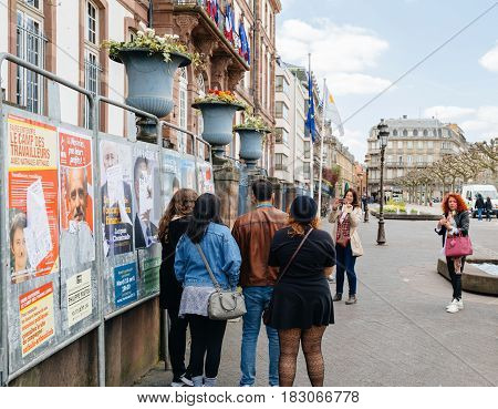 STRASBOURG FRANCE - APR 23 2017: Woman taking group photo of friends in front of campaign posters for all eleven candidates for the 2017 French presidential elections posted outside a polling station