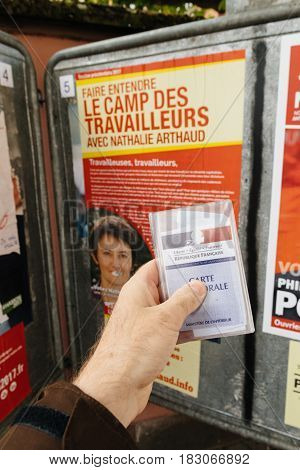 STRASBOURG FRANCE - APR 23 2017: French voter registration card held by male hand in front of official campaign poster of Nathalie Arthaud candidate for the 2017 French presidential elections posted outside a polling station