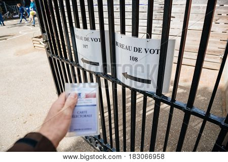 STRASBOURG FRANCE - APR 23 2017: French voter registration card held by male hand in front of Bureau de Vote Voting Section open for the 2017 French presidential elections posted outside a polling station