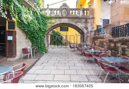 Narrow streets & charming alleys featuring dining al fresco, as an empty outdoor cafe awaits customers.  Barceloneta is Barcelona City's 18th century built neighbourhood inside the city itself.